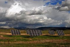 Solar Panels. In a pasture with cows and cloudy sky Royalty Free Stock Images