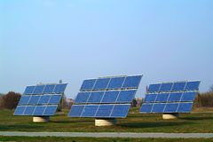 Solar Panels. Three large blue solar panels, set up in grassy field, sunshine Royalty Free Stock Photo
