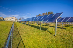 Solar panels. In field with blue sky used to furnish electricity to building Royalty Free Stock Photos