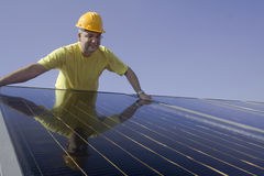 Solar panels. Worker and Solar panels on a house roof Royalty Free Stock Photo
