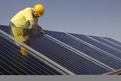 Solar panels. Worker and Solar panels on a house roof