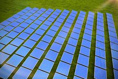 Composite image of solar panels. Solar panels against landscape with trees against sky stock illustration