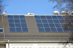 Solar panels and air conditioners on the roof of a building. Outdoor royalty free stock photos