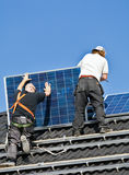 Solar panels being mounted on roof. Solar panels are being mounted on the roof of a house. This happens as part of a building project in Heerhugowaard called Stock Images