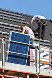 Solar panels being mounted on roof. Solar panels are being mounted on the roof of a house. This happens as part of a building project in Heerhugowaard called Royalty Free Stock Photo