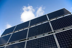 Solar panels with blue sky. Low angle view of bank of solar panels with blue sky background Royalty Free Stock Photo