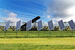 Solar panels on blue sky background. Electricity solar panels arranged in row against blue sky background. Generate power and renewable energy production Stock Image