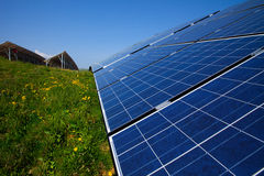 Solar panels, blue sky and green grass Stock Image