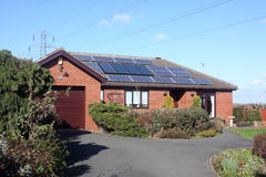 Solar Panels on Bungalow Roof. 16 Solar Panels on Bungalow Roof in UK including power lines Stock Photos