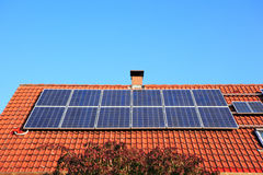 Solar panels with chimney stock photography