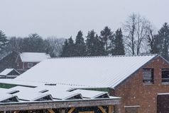 Solar panels covered in snow during snowy weather, dutch rooftops in winter season royalty free stock images