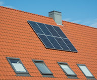Solar panels on a orange roof. Solar panels on sloping orange roof of a house Royalty Free Stock Photos