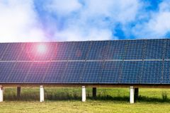 Solar Panels in a Field and Blue Sky with Clouds Stock Image