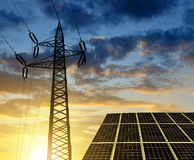 Solar panels with electricity pylon at sunset. Royalty Free Stock Image