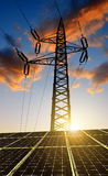 Solar panels with electricity pylon at sunset. Stock Image