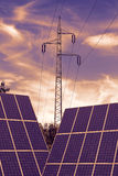 Solar panels with electricity pylon in the sunset Stock Photo