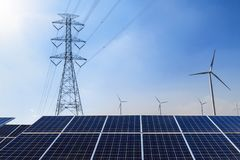 Solar panels with electricity pylon and wind turbine Clean power. Energy concept Stock Photos