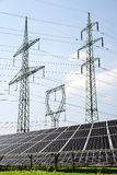 Solar panels with electricity pylons. Stock Photos