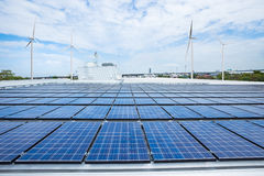 Solar panels on factory roof with wind turbine.  Royalty Free Stock Photo