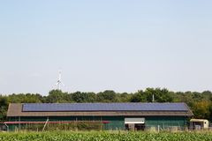 Solar panels on farming building with wind turbine in background royalty free stock image
