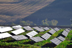 Solar panels on a field. Solar panels in a country landscape close to cultivated fields Royalty Free Stock Images