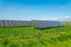 Solar panels in the field with blue sky produces renewable energy from the sun royalty free stock photography
