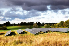 Solar panels on a field in a rural autumn landscape in the warm. Sunlight under a cloudy sky, soft focus Stock Image