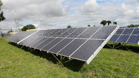Solar panels in field. Scenic view of solar panels in field with cloudscape background Royalty Free Stock Photos