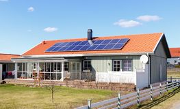 Solar panels. Gnesta, Sweden - April 10, 2016: One wooden family residential house with solar panels attached to its roof stock image