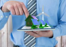 Solar panels, grass house with solar panel and windmill  on tablet. Digital composite of solar panels, grass house with solar panel and windmill  on tablet Royalty Free Stock Images