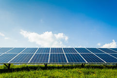 Solar panels on green field and blue sky Stock Photography