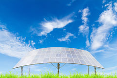 Solar panels on green grass field against blue sky background Stock Images