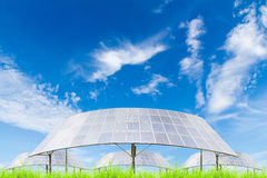 Solar panels on green grass field against blue sky background Royalty Free Stock Photos