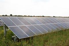 Solar panels on green grass field Stock Photos