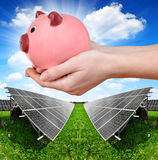 Solar panels and hand holding a pink piggy bank. Royalty Free Stock Photo