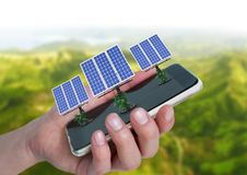 Solar panels on hand with mountains behind. Digital composite of solar panels on hand with mountains behind stock photo