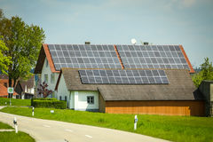 Solar panels on house roof. NANDLSTADT, GERMANY - 10.05.2017 : A village road passing next to a house with installed solar panels on the roof  in Nandlstadt Royalty Free Stock Photo