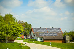 Solar panels on house roof. NANDLSTADT, GERMANY - 10.05.2017 : A village road passing next to a house with installed solar panels on the roof  in Nandlstadt Royalty Free Stock Photography