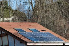 Solar panels on a house roof. Set of solar panels, photovoltaic, on the roof of a house under skylights, on forest background Royalty Free Stock Photography
