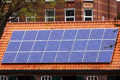 Solar panels house sky technology ecology alternative shaving economy old new roof tile cetamic encaustic. Red tile Roof with solar panels. New solar Stock Photography
