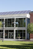 Solar Panels on Library Roof. On the front of a two story glass and brick exterior of a public library are a large array of solar panels on a sunny day in spring royalty free stock photos