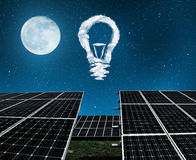 Solar panels with lightbulbs from clouds in night . Royalty Free Stock Image