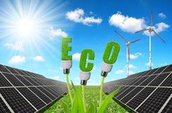 Solar panels with lightbulbs on plant against sunny sky. Royalty Free Stock Photography