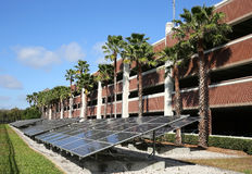 Solar panels. Long line of solar panels converting the sun`s rays into electricity in front of a parking garage stock photos