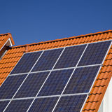 Solar panels on modern roof. Array of solar panels on roof of modern house with blue sky background Royalty Free Stock Images
