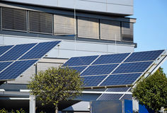 Solar panels next to an office building Stock Photos