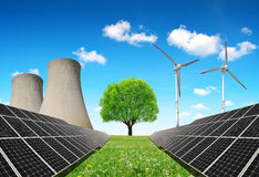 Solar panels before a nuclear power plant and wind turbines. Royalty Free Stock Image