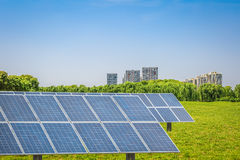 Solar panels in the park of modern city. Clean energy concept Royalty Free Stock Images