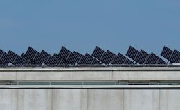 Solar panels perfectly aligned and inclined to receive the sun energy on the roof of a building.  Stock Photography