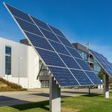 Solar panels or photovoltaic plant in front of a factory building. At a sunny day royalty free stock images